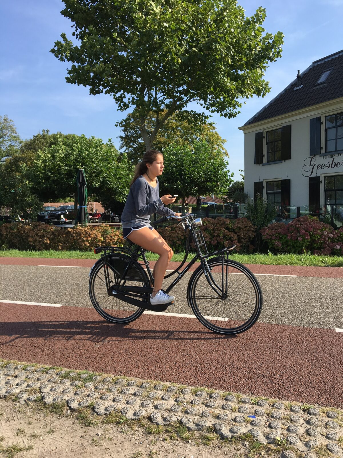 Young Dutch woman with phone on bike